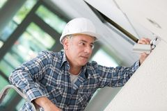 Male technician installing camera on wall. Fitting Royalty Free Stock Photos