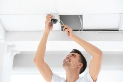 Technician installing CCTV camera on ceiling indoors. Male technician installing CCTV camera on ceiling indoors. Security system Royalty Free Stock Photo