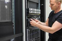 Male Technician Installing Hard Drive In Datacenter Stock Photo