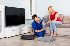 Male Technician Installing TV Set Top Box At Home. Woman Sitting On Couch Looking At Male Technician Installing TV Set Top Box At Home Stock Images