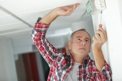 Male technician on ladder repairing sign. Man royalty free stock image
