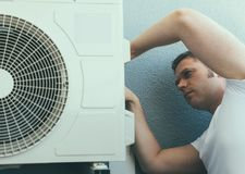 Male technician. Male technician installing air-conditioning system Stock Photos