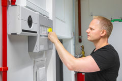 Male Technician Opening Fire Panel In Data Center. Confident mid adult male IT technician opening fire panel in data center Stock Images
