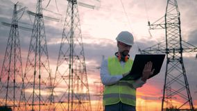 Male technician is operating a laptop beside electrical transmission lines. HD stock video