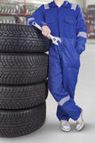 Male technician with pile of tires. Image of male technician standing near a pile of tires while holding wrench in the wheel shop Stock Photography