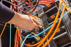 Male Technician Plugging Fiber Channel Network Cable In Blade Server Switch. Cropped hand of male technician plugging high speed fiber channel network cable in stock photo