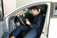 Male Technician Preparing Checklist In Car At Repair Shop. Male technician preparing checklist while sitting in car at an automobile repair shop Royalty Free Stock Photography