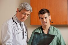 Male Technician With Radiologist. Portrait of male technician with mature doctor reviewing shoulder x-ray Royalty Free Stock Image