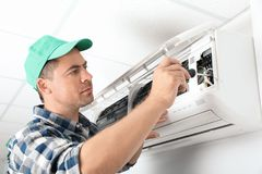 Male technician repairing air conditioner. Indoors Stock Photo
