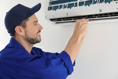 Male technician repairing air conditioner. Indoors Royalty Free Stock Image