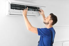 Male technician repairing air conditioner. Indoors Royalty Free Stock Images