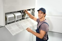 Male technician repairing air conditioner. Indoors Stock Photos