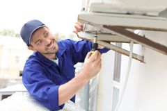 Male technician repairing air conditioner. Outdoors Stock Photo