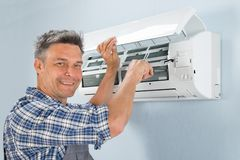 Male technician repairing air conditioner. Portrait Of A Happy Male Technician Repairing Air Conditioner Stock Photos