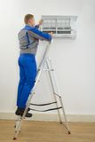 Male technician repairing air conditioner. Standing On Stepladder Stock Photography