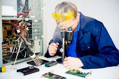 Male technician repairing a computer. Portrait of a male technician repairing a broken computer Royalty Free Stock Image
