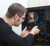 Male technician repairing computer. At store Royalty Free Stock Photos