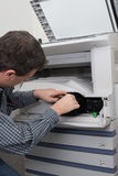 Male technician repairing digital photocopier machine Stock Photos