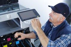 Male technician repairing digital photocopier machine. Copy Royalty Free Stock Images