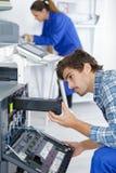 Male technician repairing digital photocopier machine. Man Stock Photo