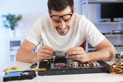 Male technician repairing motherboard at table stock image