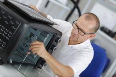 Male technician repairing oven. Repairing Stock Images
