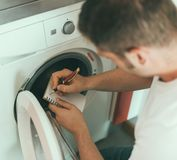 Male technician repairing washing machine. Male technician repairing washing machine, writing the manufacturer`s code Royalty Free Stock Image