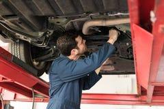 Male Technician Servicing Car In Repair Shop. Side view of mid adult male technician servicing car in repair shop stock photos