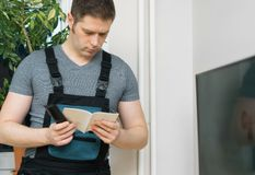 Male setting up TV. Male technician setting up new TV with instruction stock image