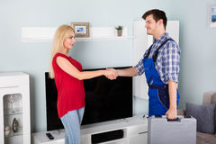 Male Technician Shaking Hand With Woman. Young Male Technician Shaking Hand With Smiling Young Woman At Home Royalty Free Stock Photography