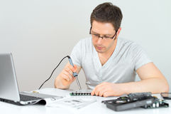 Male technician. Male technician soldering lan switch router at his workplace Stock Image