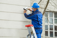 Male Technician Standing On Stepladder Fitting CCTV Camera. Mature Male Technician Standing On Stepladder Fitting CCTV Camera On Wall Stock Photography