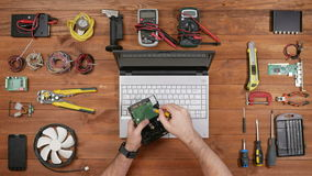 Male technician to disassemble the hard disk to be checked. Wooden table top view stock video footage