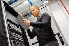 Male Technician Using Digital Tablet In Datacenter to Monitor SAN and Servers. Confident male technician using digital tablet standing in datacenter to monitor stock image