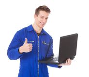 Male technician using laptop. Young Male Technician Using Laptop Over White Background Royalty Free Stock Photos