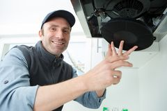 Male technician working on kitchen extractor filter royalty free stock photo