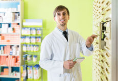 Male technician working in pharmacy depot. Positive russian male technician working in pharmacy depot Royalty Free Stock Images