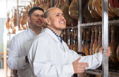 Male technologists in white gown checking joints of iberico jamo. Butchery male technologists in white gown checking joints of iberico jamon Royalty Free Stock Image