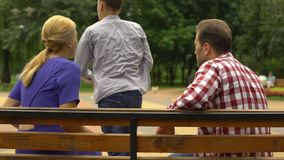 Male teen arguing with parents on bench and walking away, adolescence problems. Stock footage stock video
