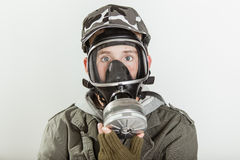 Male teen with face covered by respirator. Close up of single male teen in jacket, brown gloves and gray camouflage hat holding a fire fighter respirator gas Stock Images