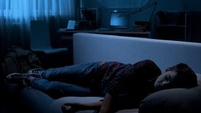 Male teen fallen asleep on couch in front of TV, free time at home, awkward age royalty free stock photography