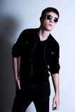 Male Teen Looking Cool in Sunglasses. Male teen in sunglasses and hip clothing poses against a solid white background. Vertical shot Stock Image