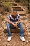 Male teen sitting on trail. Handsome African-American male sitting in natural surroundings Royalty Free Stock Photo
