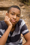 Male teen sitting on trail. Handsome African-American male sitting in natural surroundings Stock Photo