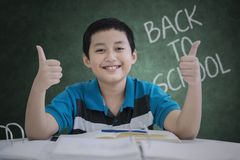 Male teen student showing thumbs up. Picture of male teen student looks happy while showing thumbs up with text of back to school on the chalkboard Royalty Free Stock Photo