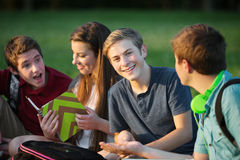 Male Teen Studying with Friends. Happy male teen sitting with students outdoors Stock Photography