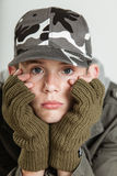 Male teen sulking while holding face in gloves. Close up of single male teen in jacket, brown gloves and gray camouflage hat holding his sulking face in hands Stock Image