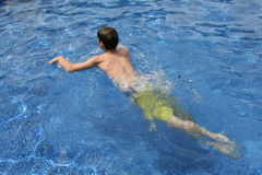 Male teen swimming in water. Male teen swimming in blue water in the summer Royalty Free Stock Photography