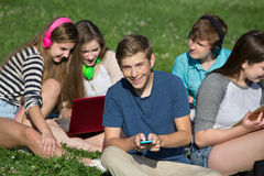 Male Teen Texting. Group of cheerful students texting and studying Stock Photography