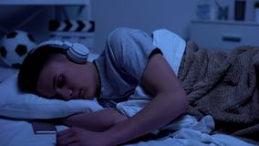 Male teenage boy fallen asleep in headphones, overworked student relaxing. Stock photo royalty free stock images